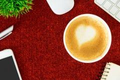Un café de latte avec du lait de coeur d'art sur la table rouge de bureau de à Photos stock