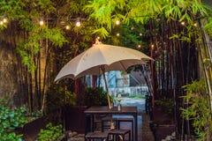 Un café de rue avec un parapluie et des lumières photo stock