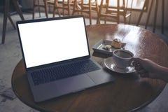 Un café et un ordinateur portable potables de femme avec l'écran blanc vide sur la table en bois en café Photos libres de droits