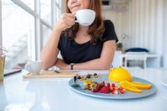 Un caffè bevente della bella donna asiatica e mangiare dolce arancio con frutta mista fotografia stock libera da diritti