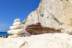 Un cairn è situato davanti al relitto della nave sulla spiaggia di Navagio sull'isola di Zacinto, Grecia fotografie stock libere da diritti