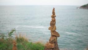 Un cairn è supporti sopra una scogliera contro il mare blu Mucchio del primo piano delle pietre video d archivio