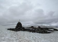 Un cairn che segna una traccia di escursione di Laugavegur coperta di neve, riserva naturale di Fjallabak, altopiani dell'Islanda immagine stock