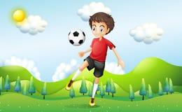 Un calcio di pratica del ragazzo alla collina Fotografie Stock