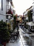 Un callejón típico del pueblo en España con los cafés, las flores y la gente caminando después de lluvia fotografía de archivo libre de regalías