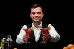 Un camarero atractivo con dos vidrios del margarita por completo de los cócteles, naranjas, limón, una coctelera en un fondo negr Fotos de archivo libres de regalías