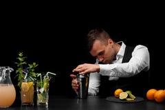 Un camarero atractivo limpia una coctelera, un contador de la barra con los cócteles, las cales, el limón y naranjas en un fondo  Fotos de archivo