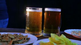 Un camarero de sexo femenino pone una tabla con bocados en las tazas llenas de un fondo dos negros de cerveza que hace espuma almacen de metraje de vídeo