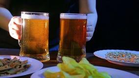 Un camarero de sexo femenino pone una tabla con bocados en las tazas llenas de un fondo dos negros de cerveza que hace espuma metrajes