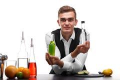 Un camarero detrás de un contador de la barra con los ingredientes para los cócteles, aislados en un fondo blanco Servicio del re Fotos de archivo