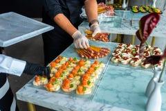 Un camarero en guantes en un banquete prepara una tabla imágenes de archivo libres de regalías