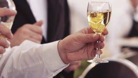 Un camarero está vertiendo el vino blanco en la copa Retrato masculino, tiroteo exterior Burbujas del vino Banquete de boda itali almacen de video