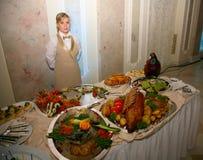 Un camarero hermoso de la chica joven presenta una comida fría impresionante en un restaurante ruso Fotos de archivo