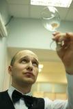 Un camarero hermoso que mira el vidrio Foto de archivo