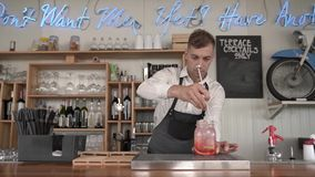 Un camarero joven hermoso hace una limonada fresca, fresca del color rojo en el contador de la barra almacen de metraje de vídeo