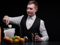Un camarero profesional detrás de un contador de la barra Frutas cítricas, hielo y una coctelera en un fondo negro Fabricación de Imagen de archivo
