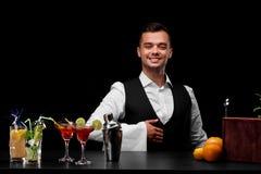 Un camarero profesional e ingredientes del cóctel en un fondo negro Concepto del restaurante y del club Copie el espacio Imagenes de archivo