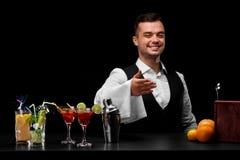 Un camarero profesional e ingredientes del cóctel en un fondo negro Concepto del restaurante y del club Copie el espacio Foto de archivo