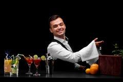 Un camarero profesional e ingredientes del cóctel en un fondo negro Concepto del restaurante y del club Copie el espacio Imagen de archivo libre de regalías