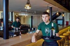 Un camarero que sostiene una bandeja con la botella de vino y de vidrios en barra imagen de archivo libre de regalías
