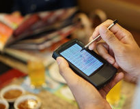 Un camarero que usa un bolsillo de la PC, tecnología del PDA, Fotografía de archivo libre de regalías