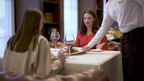 Un camarero trae un plato sabroso a dos muchachas que se sientan en una tabla en un restaurante Dos novias en un buen resto del h almacen de metraje de vídeo