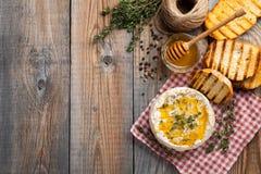 Un camembert real de Francia con tomillo, miel y pan tostado en la tabla rústica de madera vieja Queso suave en los wi de madera  foto de archivo libre de regalías