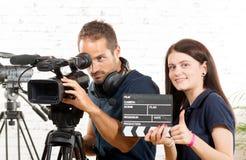 Un cameraman y una mujer con una cámara de película Foto de archivo