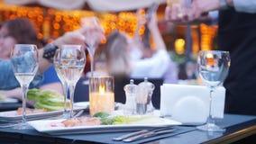 Un cameriere parla delle bevande e rovescia l'alcool nel vetro - aria aperta del ristorante video d archivio