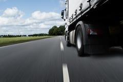 Un camión con el remolque se mueve rápidamente a lo largo de un camino foto de archivo libre de regalías