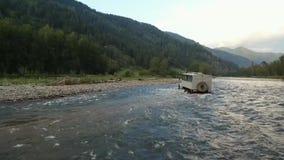 Un camión cruza un río de la montaña almacen de metraje de vídeo