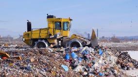 Un camión del vertido nivela la primera capa de la basura en un depósito de chatarra metrajes