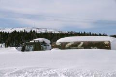 Un camión se está oponiendo en una nieve acumulada por la ventisca a un fondo del bosque Fotos de archivo