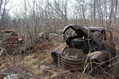 Un camión viejo y otros vehículos abandonados en el bosque durante los meses de invierno Imagen de archivo