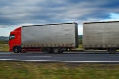 Un camión con un remolque en el camino en el campo Foto de archivo