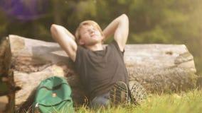 Un caminante masculino joven viene a un tronco caido del árbol sentarse y descansar en la luz del sol almacen de metraje de vídeo
