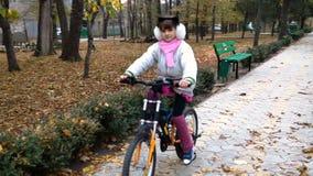 Un camino caucásico de la bici de los paseos de los niños en parque almacen de metraje de vídeo