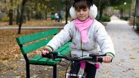 Un camino caucásico de la bici de los paseos de los niños en parque del otoño metrajes