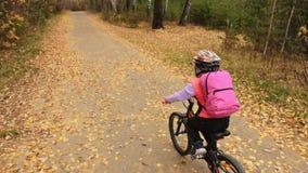 Un camino caucásico de la bici de los paseos de los niños en parque del otoño El ciclo anaranjado negro del montar a caballo de l almacen de metraje de vídeo