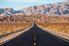 Un camino corre en el parque nacional de Death Valley, California, los E.E.U.U. Imagen de archivo