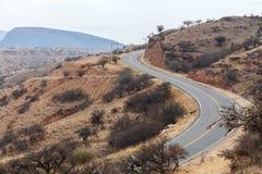 Un camino de la montaña de la bobina que corre a través del terreno árido del Oriente Medio Fotos de archivo libres de regalías
