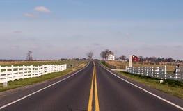 Un camino de las tierras de labrantío debajo de un cielo azul Fotos de archivo