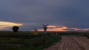 Un camino de tierra cerrado sobre un cruce ferroviario con una puesta del sol imágenes de archivo libres de regalías