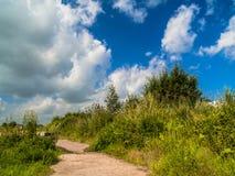 Un camino de tierra corre a lo largo de la colina Foto de archivo libre de regalías