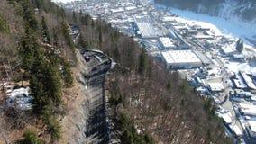 Un camino en las montañas con la ciudad abajo de la colina, cantidad aérea en 4k almacen de metraje de vídeo