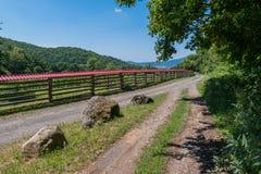 Un camino espacioso en las montañas, separadas por una cerca de madera alta con un tejado rojo fotografía de archivo