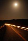 Un camino iluminado por la luna con los rastros del coche Fotos de archivo libres de regalías