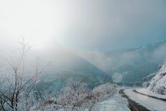 Un camino peligroso de la serpentina del invierno con las muestras de la atención cubiertas fotografía de archivo