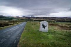 Un camino a través de los fileds en Escocia con una señal de peligro del águila Foto de archivo