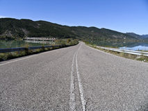 Un camino vacío al lado de un lago, Fotos de archivo libres de regalías
